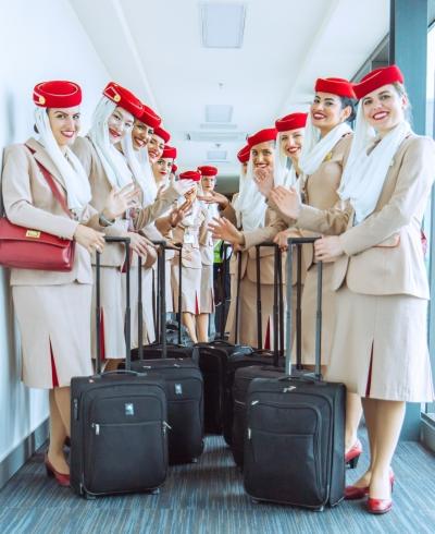Stewardessen der Airlines Emirates mit roten Hütchen mit Schleier und in beigen Kostümen mit schwarzen Koffern