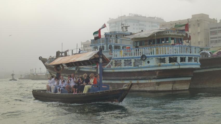 Abras, Holzboote, dienen als Taxi über den Dubai Creek. Im Hintergrund ein Transportschiff aus Holz