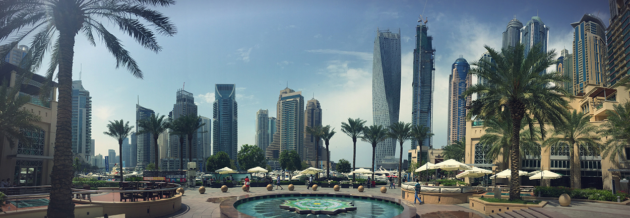 Foto von einem Platz in Dubai mit zahlreichen Wolkenkratzern rundherum. Dazwischen Palmen, kleine Brunnen und Plätze mit Sonnenschirmen zum Ausruhen