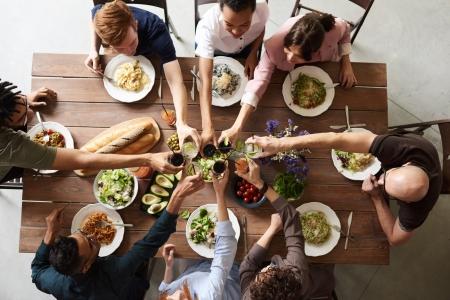 8 Personen sitzen an einem gedeckten Tisch und stoßen zusammen mit Gläsern an