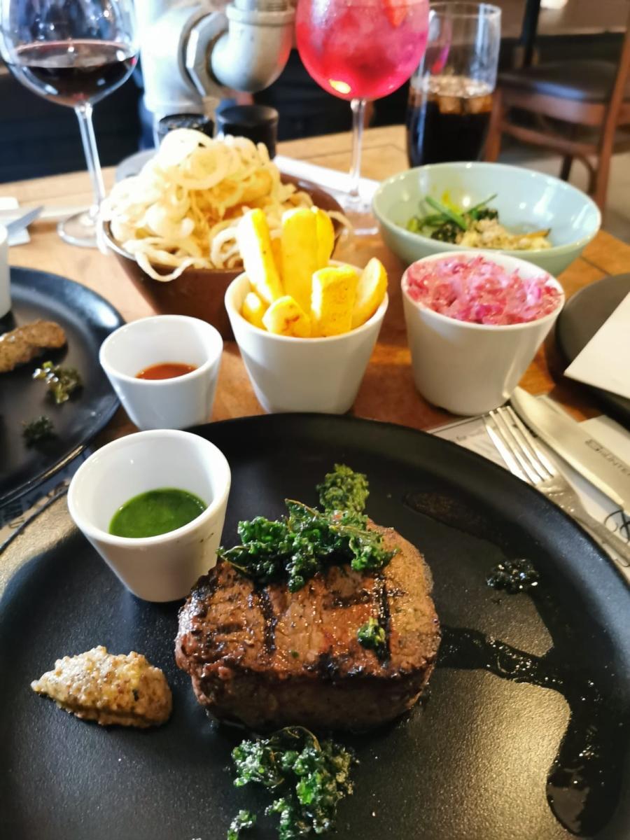 Im Restaurant Char'd wird ein saftiges Steak mit vielen Beilagen serviert