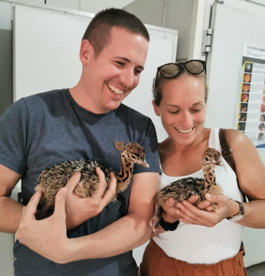 Jessi und ihr Freund halten zwei Straußenbabys in den Händen