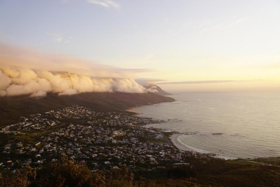 Sonnenuntergang mit Blick auf den Tafelberg, eingehüllt in Wolken, am Fuße des Berges liegt Kapstadt