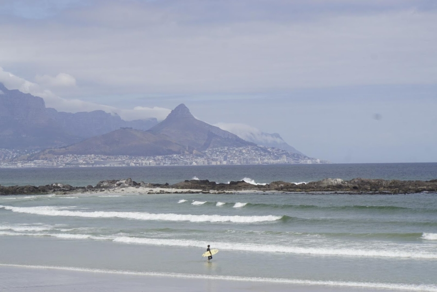 Ein Surfer am Blouberg Strand - im Hintergrund Kapstadt und der Berg Lions Head