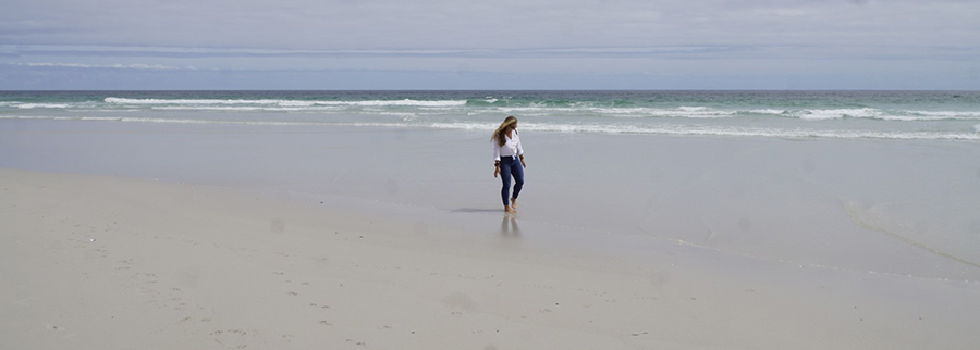 Jessi am breiten und menschenleeren von Noordhoek Beach, Südafrika