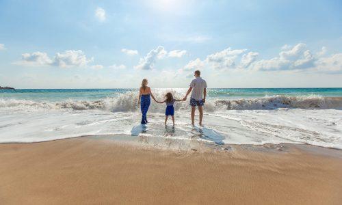 Servus Urlaub - Mutter, Tochter und Vater stehen Hand in Hand am Strand und eine Welle rollt heran